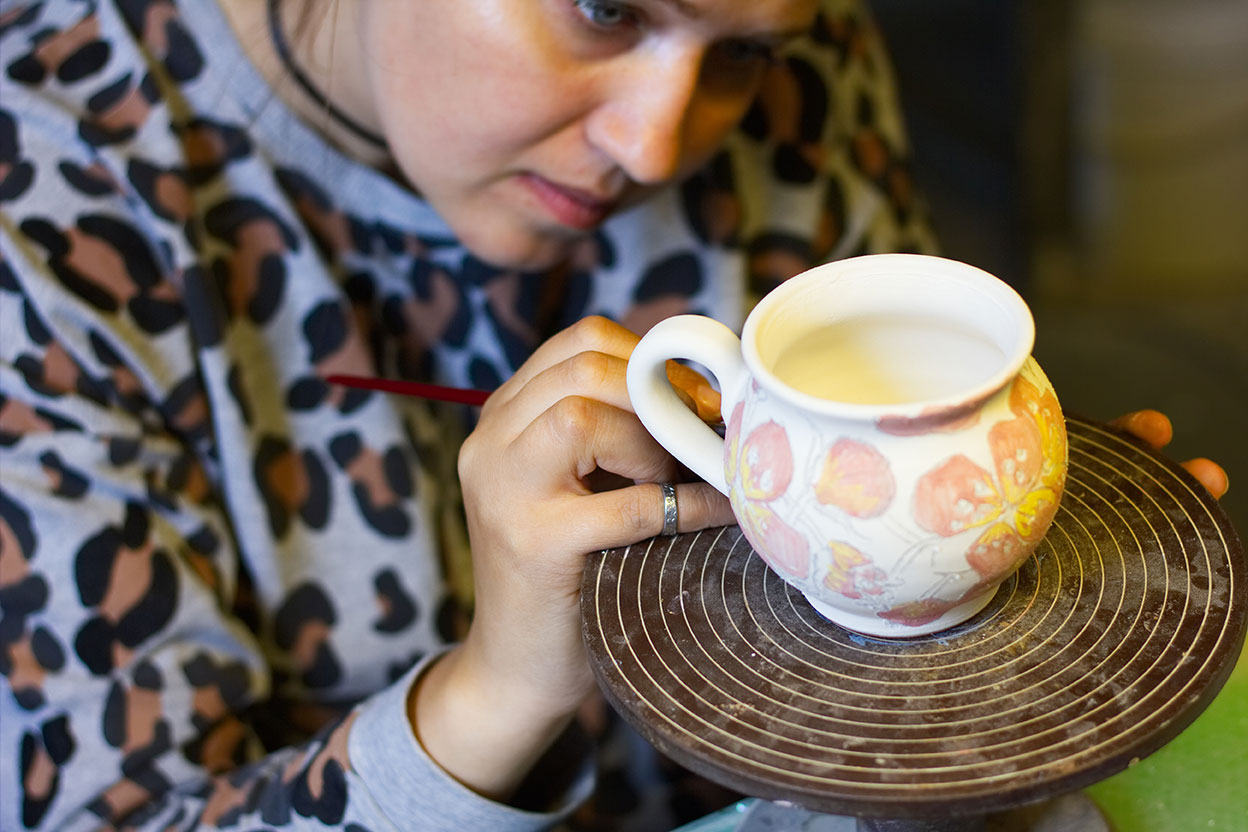 Frau beim Keramikmalen im Eigenlob.